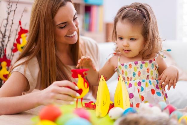 Jonge moeder speelt met haar baby in pasen-tijd