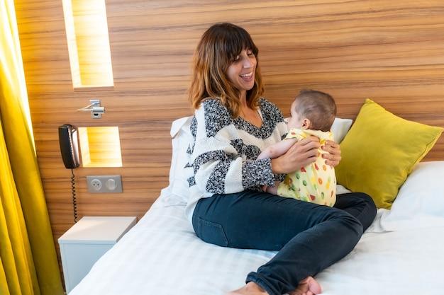 Jonge moeder speelt met haar baby op het bed in haar slaapkamer, levensstijlportret van een jonge moeder, familie thuis