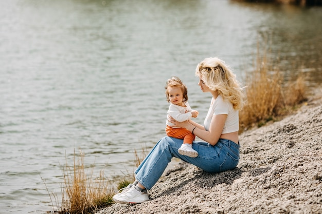 Jonge moeder speelt met haar dochter buiten aan het meer