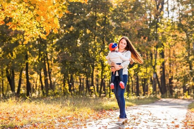 Jonge moeder speelt met haar dochter in het herfstpark.