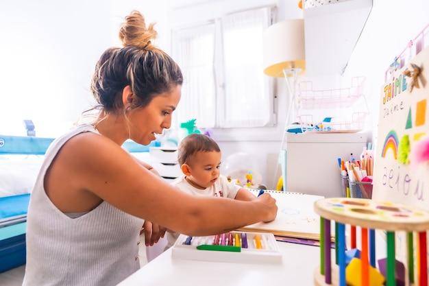 Jonge moeder speelt met haar in de kamer met speelgoed
