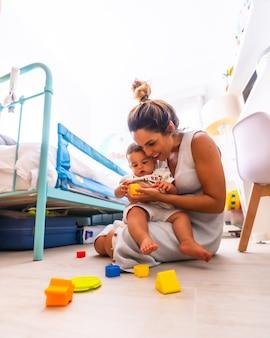 Jonge moeder speelt met haar kind in de kamer met speelgoed