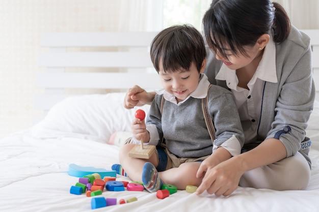 Jonge moeder speelt met mooie zoon in de slaapkamer