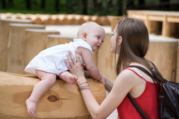 Jonge moeder speelt met schattige baby. kind lacht haar moeder. buiten levensstijl.