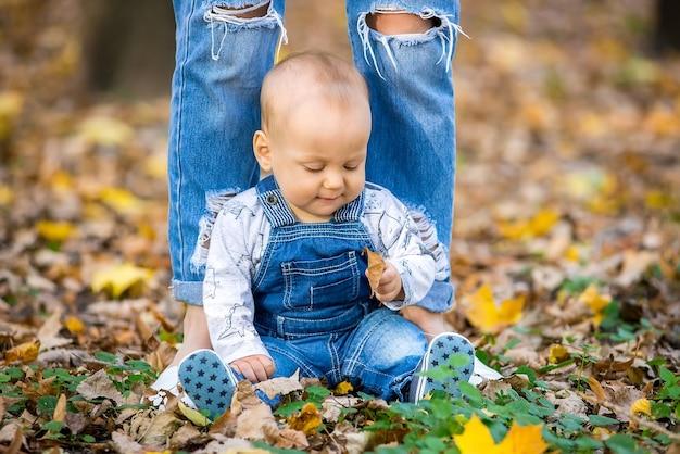 Jonge moeder spelen met baby in herfst park