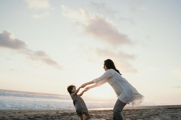 Jonge moeder spelen met haar kleine meisje aan zee