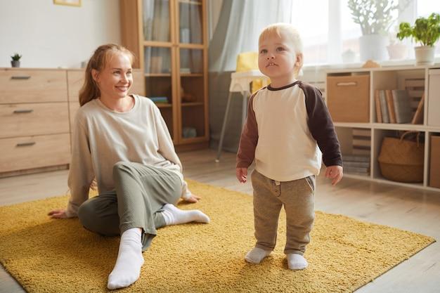 Jonge moeder spelen op de vloer met haar babyjongen in de huiskamer