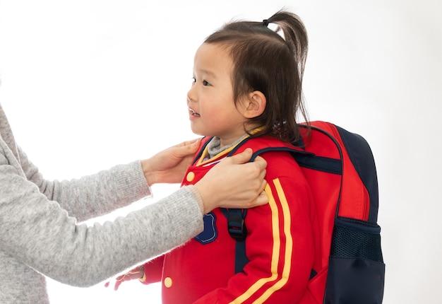 Jonge moeder stuurt haar dochter naar de kleuterschool