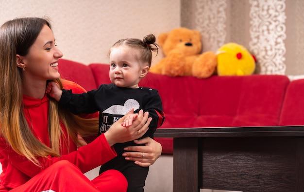 Jonge moeder ter ondersteuning van haar dochtertje staande lachend als het kleine meisje