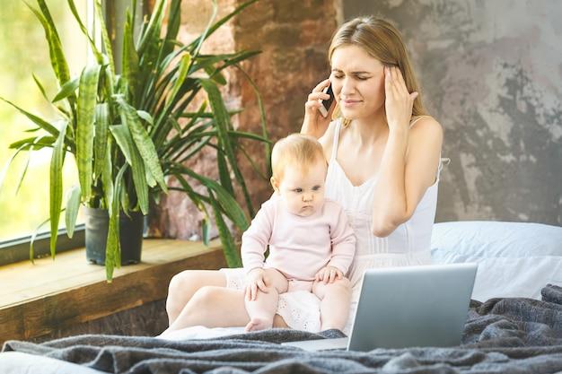 Jonge moeder thuiswerken, praten over smartphone terwijl ze tijd doorbrengen met haar babymeisje. freelance. thuis werken. in stress.