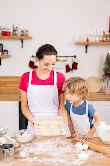 Jonge moeder toont haar zoon rauwe koekjes die ze samen hadden gemaakt voordat ze ze in de oven legden om te bakken