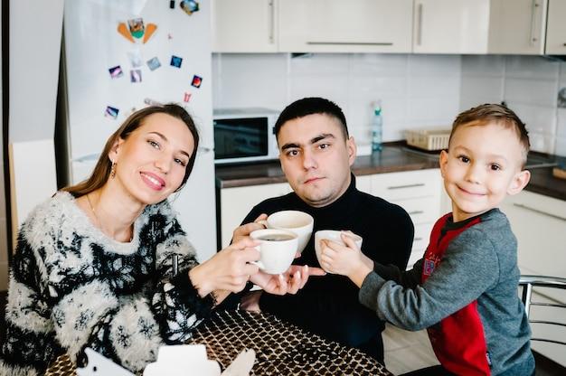 Jonge moeder, vader en jongen die 's ochtends koffie en thee drinken. gelukkige moeder, vader en zoon die thuis in de keuken ontbijten. familie, eten en mensen concept.