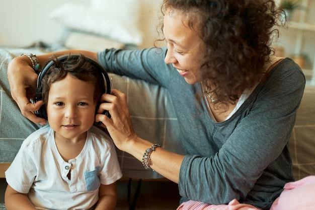 Jonge moeder van gemengd ras die op haar schattige driejarige zoon past, met behulp van een draadloze headset
