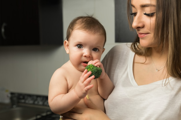 Jonge moeder voedt babybroccoli.