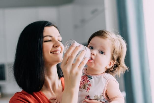 Jonge moeder voedt haar baby uit de fles in de keuken