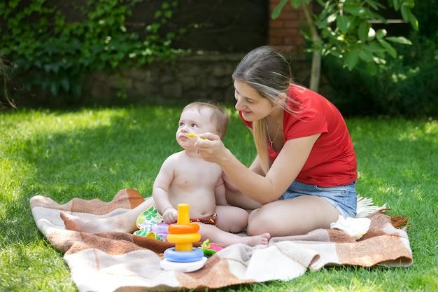 Jonge moeder voedt haar babyjongen op gras in het park