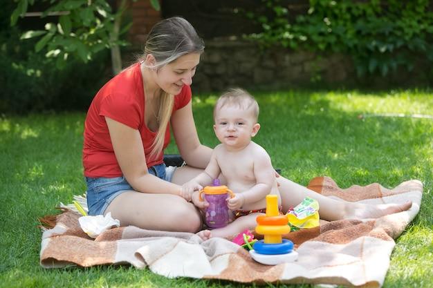 Jonge moeder voedt haar zoontje op picknick in het park