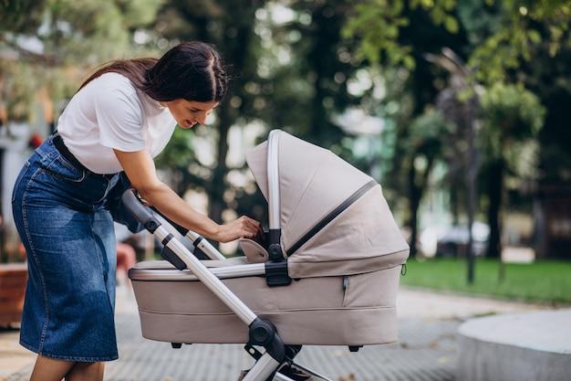 Jonge moeder wandelen met kinderwagen in park