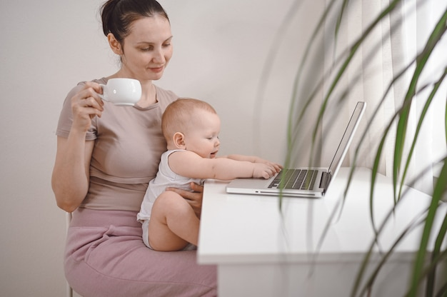 Jonge moeder werk studeren vanuit huis met laptop, kleine schattige peuter baby op schoot.