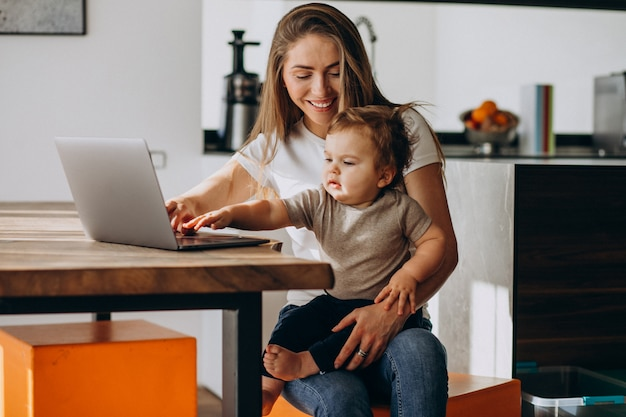 Jonge moeder werkt vanuit huis op laptop met haar zoontje