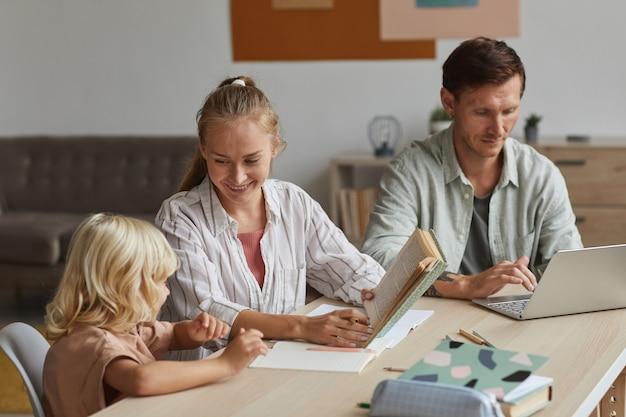 Jonge moeder zit aan de tafel met haar zoon en leest hem een boek, ze helpt hem om huiswerk te maken