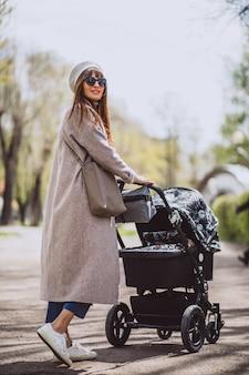 Jonge moeder zit met kinderwagen in park