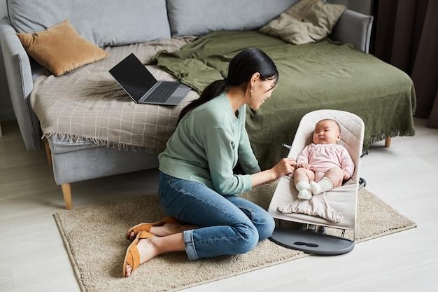 Jonge moeder zit op de grond en praat met haar dochtertje in de woonkamer