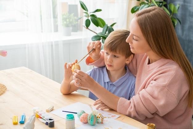 Jonge moeder zittend aan tafel met verfblikken en verf toe te voegen aan zonen easter egg terwijl ze pasen decoraties maken