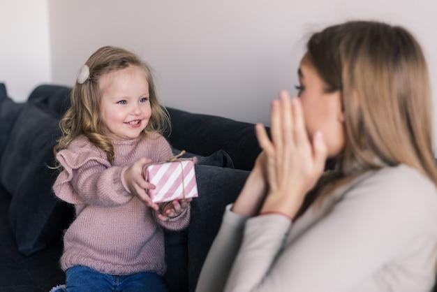 Jonge moeder zittend op de bank thuis ontving een verrassing van haar dochter die met verbazing naar het geschenk keek op moederdag