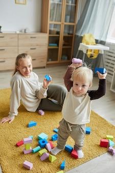 Jonge moeder zittend op de vloer en kijken naar haar kind terwijl hij met speelgoed in de kamer speelt
