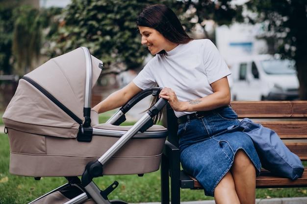 Jonge moeder zittend op een bankje in park met kinderwagen