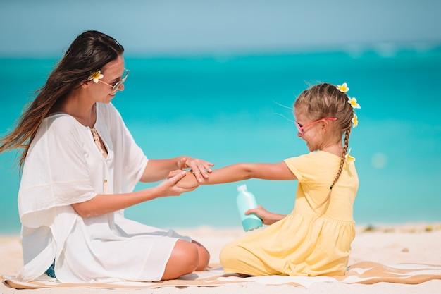 Jonge moeder zonnebrandcrème toe te passen op dochter neus op het strand. zon bescherming