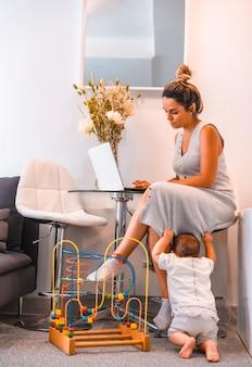 Jonge moeder zorgt voor haar jonge zoon en telewerken vanuit huis