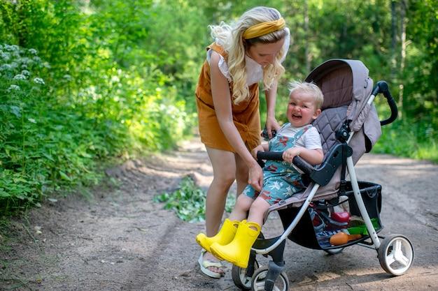 Jonge moeder zorgt voor huilende zoon zit in de kinderwagen in het bos