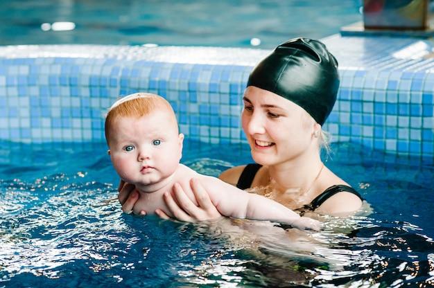 Jonge moeder, zweminstructeur en gelukkig meisje in peuterbad. leert het kind om te zwemmen. geniet van de eerste dag zwemmen in water. het mamma houdt handkind voorbereidend voor het duiken. oefeningen doen