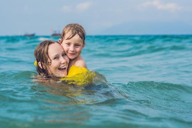 Jonge moeder zwemmen en spelen met mannelijke kind jongen in zee of oceaan water s