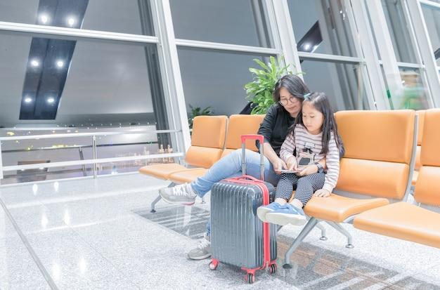 Jonge moederbespreking met haar dochter over reis op stoel in luchthaven, reisconcept