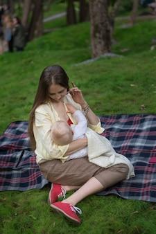 Jonge moederborst die haar baby op aardachtergrond voeden.