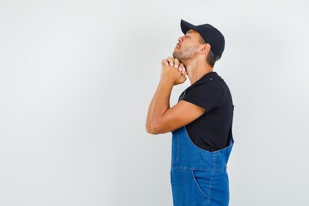Jonge monteur omklemde handen in biddend gebaar in uniform en op zoek hoopvol. .