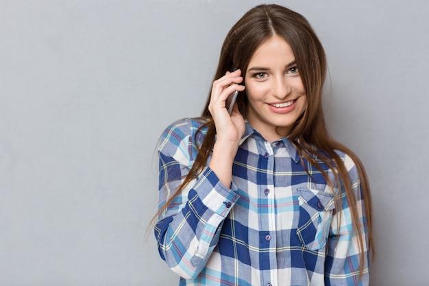 Jonge mooie aantrekkelijke gelukkige vrouw in geruit hemd praten op mobiele telefoon en glimlachen