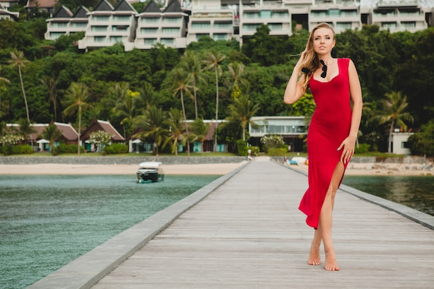 Jonge mooie aantrekkelijke vrouw die alleen staat op de pier in een luxe resorthotel, zomervakantie, rode lange jurk, blond haar, sexy kleding, tropisch strand, verleidelijk, sensueel, glimlachen