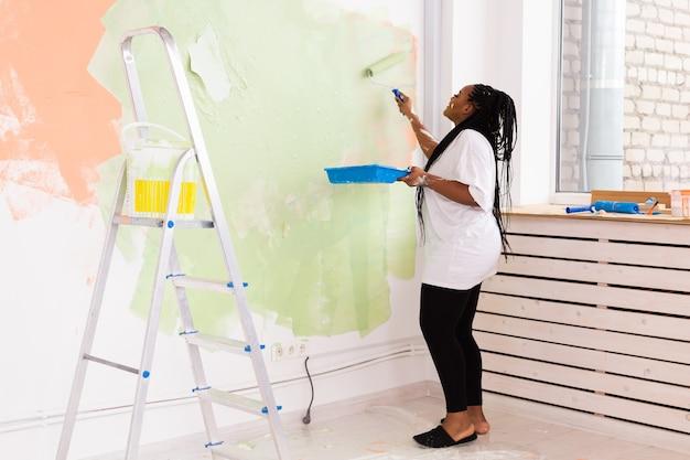 Jonge mooie african american vrouw schilderij muur in haar nieuwe appartement.