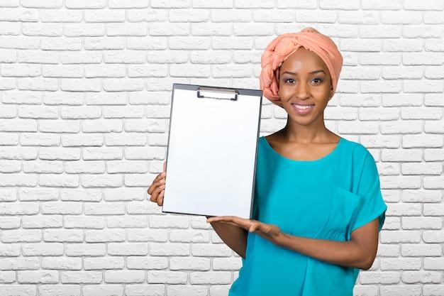 Jonge mooie afrikaanse amerikaanse vrouw die klembord toont