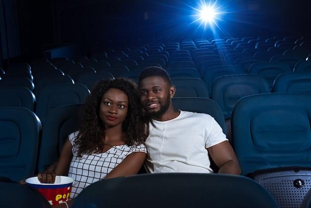 Jonge mooie afrikaanse paar kijken naar een film knuffelen in de plaatselijke bioscoop
