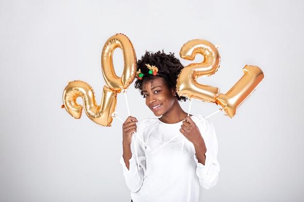 Jonge mooie afrikaanse rendierhoorns op haar hoofd met ballonnen 2021 in haar handen
