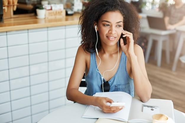 Jonge mooie afrikaanse studente die aan muziek in hoofdtelefoons luisteren die zitting bij lijst met boeken bij koffie glimlachen.