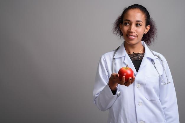 Jonge mooie afrikaanse vrouw arts tegen grijze muur