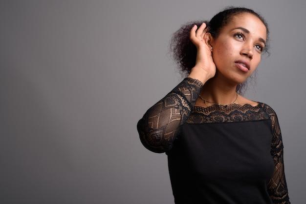 Jonge mooie afrikaanse vrouw op grijs