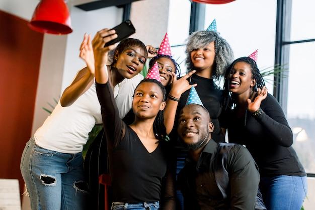 Jonge mooie afro-amerikaanse meisjes vieren hun verjaardag en maken een selfii op hun smartphone.