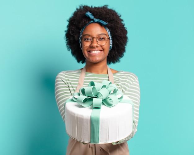 Jonge mooie afro-bakkersvrouw met een verjaardagstaart